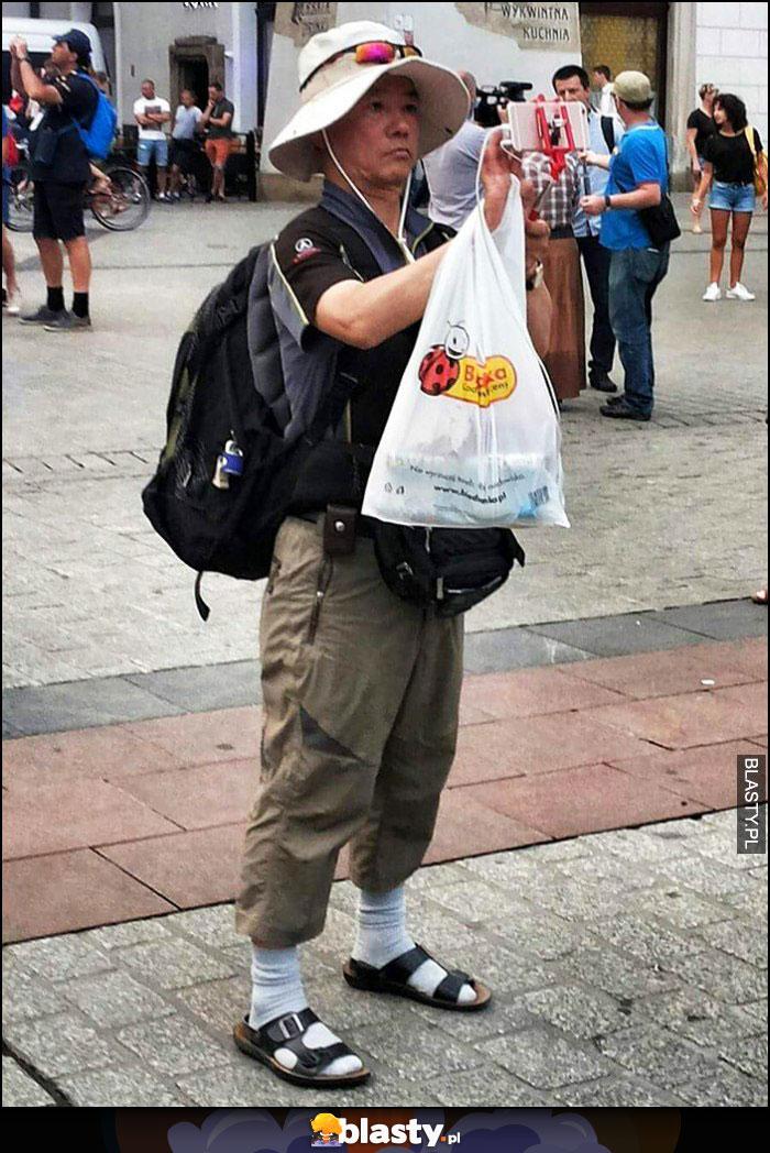Turysta z Japonii białe skarpety, sandały, reklamówka z Biedronki Biedry
